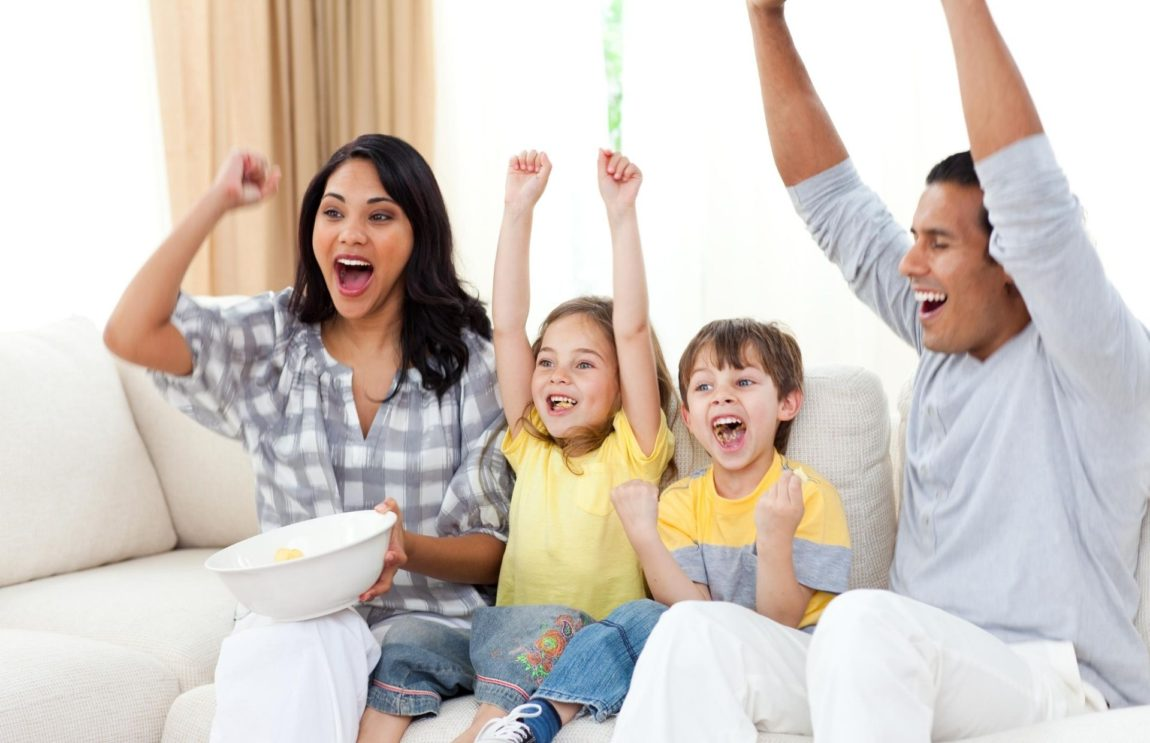 a family watching the best disney+ shows for families on the couch
